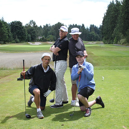 Four white men pose at a hole on a golf course