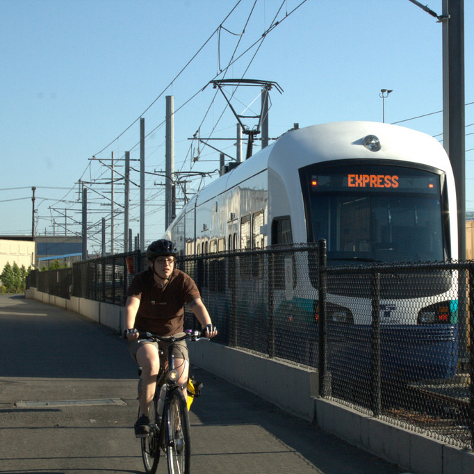 Bicyclist rides next to Seattle light rail train